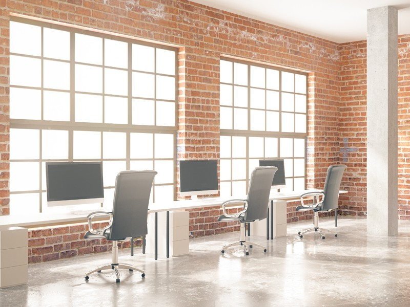 Side view of coworking office interior with computers, concrete floor, red brick walls, columns and windows. 3D Rendering