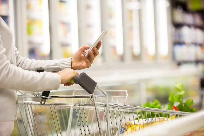 Woman using mobile phone while shopping in supermarket, trolley, frozen department store
