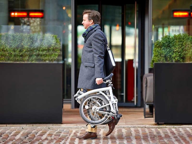 Middle aged businessman carrying his folding bicycle on sidewalk by the street